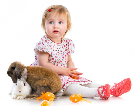 Easter photos  Cute little girl in a summer dress with two rabbits on white background photo