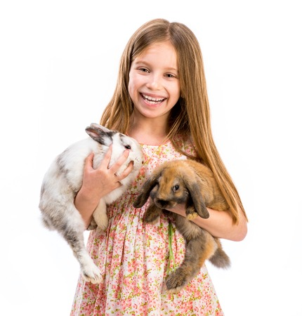 cute smiling girl in a summer dress with two baby rabbits photo