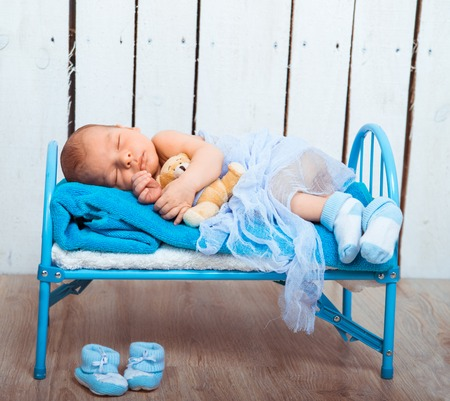 0 1 months: Cute newborn baby sleeps in a small bed with teddy bear Stock Photo