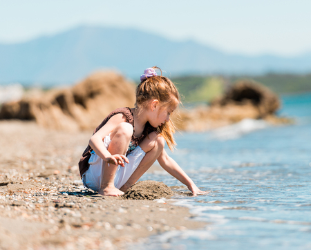 Pebble Beach: little girl sitting on the beach builds a tower Stock Photo