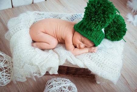 Cute newborn baby sleeps in a green hat photo