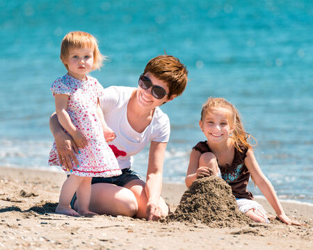 mother and daughters playing in the sand photo