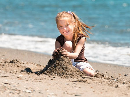 happy little girl sitting on the beach builds a tower of sand