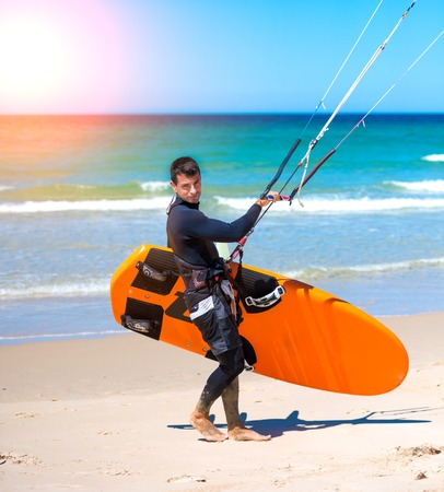 kite surfing: young handsome athlete going to kite surfing training