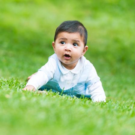 latin child: little Spanish boy on the green grass