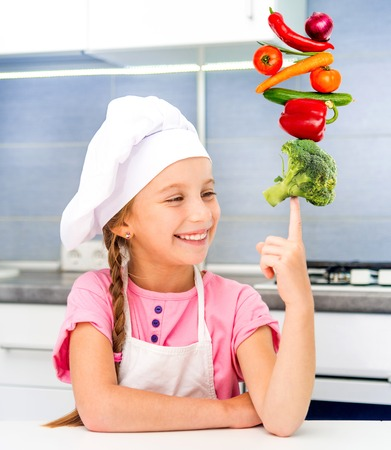 little girl dressed as a cook balanced pyramid of vegetables photo