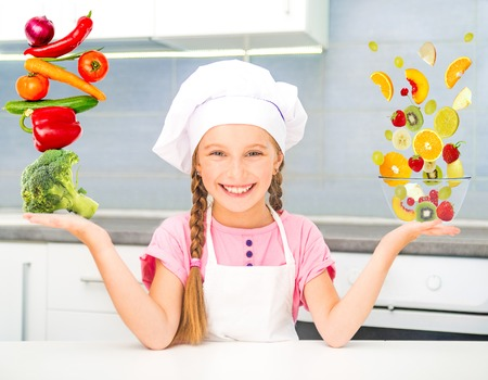 little girl dressed as a cook balanced pyramid of vegetables and fruits photo