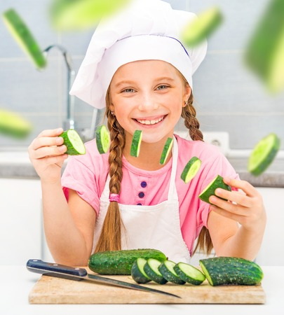 smiling little girl cuts cucumbers home in the kitchen photo
