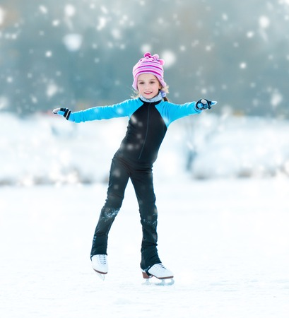 cute cheerful little girl in thermal suits skating outdoors photo
