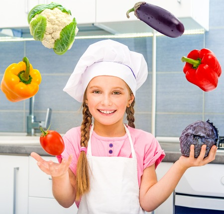 smiling little girl juggle vegetables home in the kitchen photo