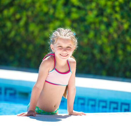 smiling cute little girl swims with a lifeline in the pool photo