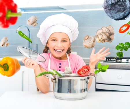 happy little girl preparing vegetarian soup in the kitchen photo