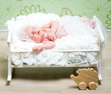 0 3 months: beautiful newborn baby boy sleeps in a small bed in white knitted cap