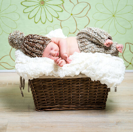 0 3 months: beautiful newborn baby boy asleep in a wicker basket in knitted cap