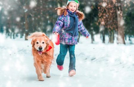 Schöne kleine Mädchen mit ihrem Hund auf dem Schnee im Winter