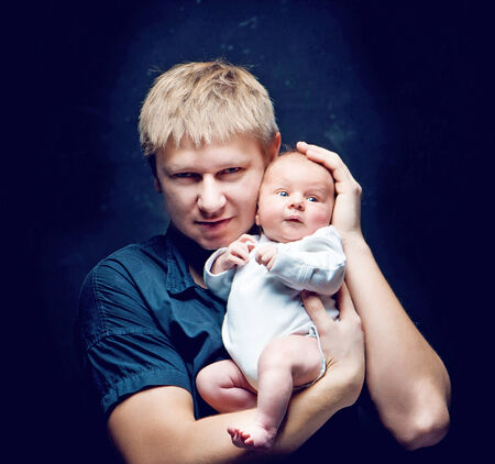 father and his newborn baby daughter over black background photo