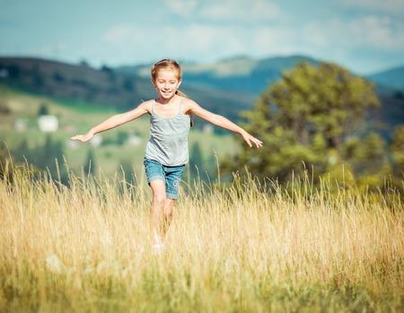 어린 소녀는 아름다운 초원 통해 실행