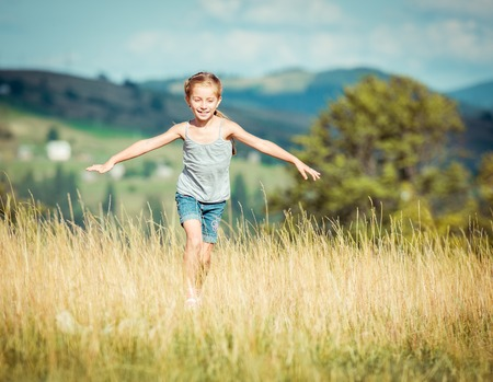 little girl runs through a beautiful meadow Foto de archivo