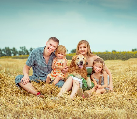 happy parents and two daughters with dog photo
