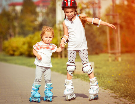 two little sisters to roller skate on the street photo