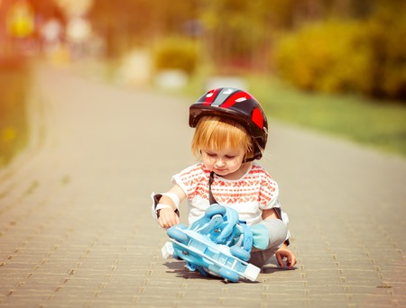 rollerskater: two year old pretty girl in roller skates and a helmet sitting on the street Stock Photo
