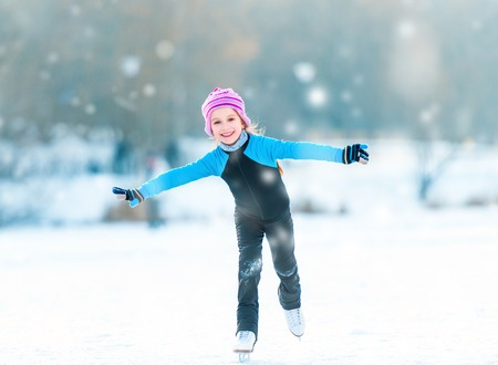 pretty cheerful little girl in thermal suits skating outdoors Banque d'images