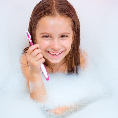 bathwater: Cute girl brushing teeth in bath
