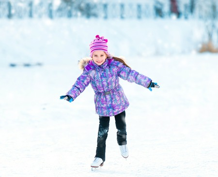 Happy little girl skating in winter outdoors