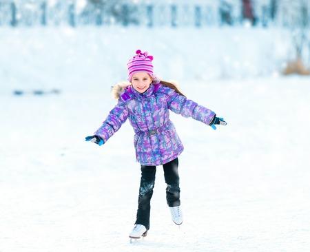 patinaje sobre hielo: Niña feliz de patinaje en invierno al aire libre Foto de archivo