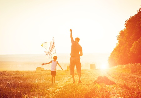 Dad with his little daughter let a kite in a field photo