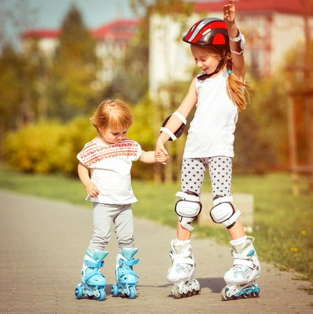 rollerskater: two little sisters to roller skate on the street, back view