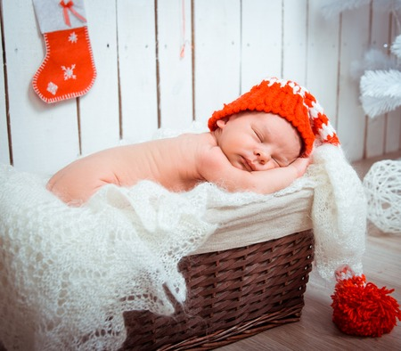 0 6 months: Cute newborn baby sleeps in a santa claus hat close-up Stock Photo