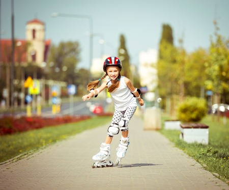rollerskater: little cute happy girl rollerblading through the city streets