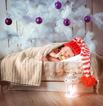 0 1 months: Cute newborn baby sleeps in a santa claus hat close-up Stock Photo