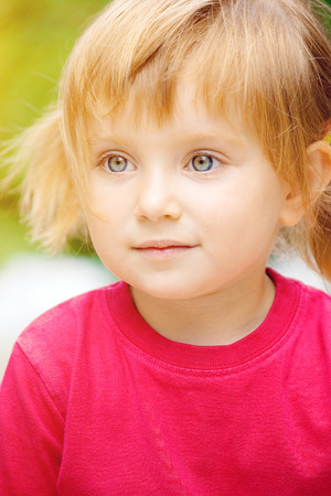 3 persons only: Cute liitle girl in a red t-shirt close-up Stock Photo