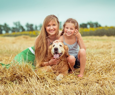 lovely family: mother and daughter with a dog in field photo