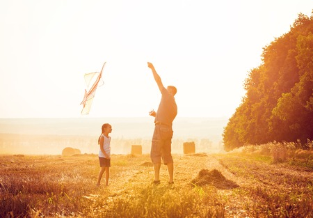 father and daughter: Dad with daughter let a kite in a field