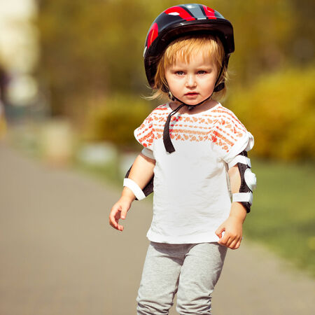 two year old: two year old pretty girl in roller skates and a helmet sitting on the street Stock Photo