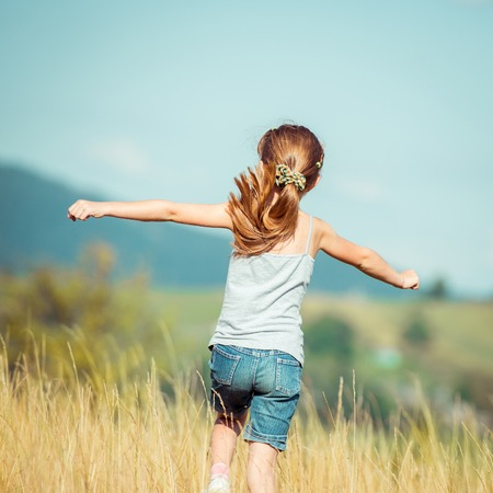 little girl runs through a beautiful meadow in the mountains. back view Banque d'images