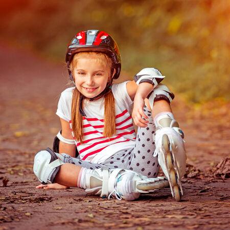 rollerskater: happy little girl sitting on roller skates in the autumn forest