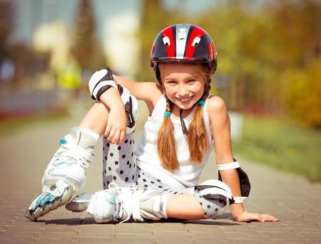 rollerskater: Little girl in roller skates sitting on a city street