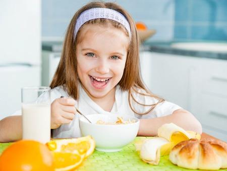 cereales: linda ni�a comiendo cereales con la leche en la cocina Foto de archivo