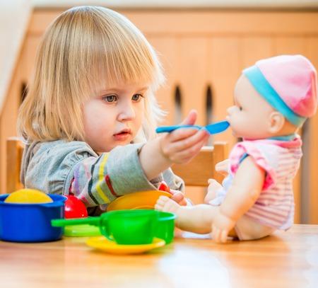 meisje voederen een pop thuis in de kinderkamer Stockfoto