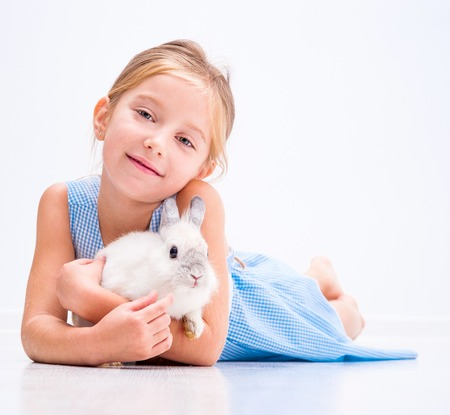 cute smiling girl in a blue dress with a white rabbit Reklamní fotografie - 33199625