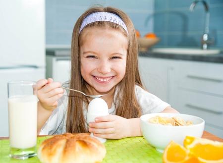 comiendo cereal: Niña bonita que come huevo en la cocina