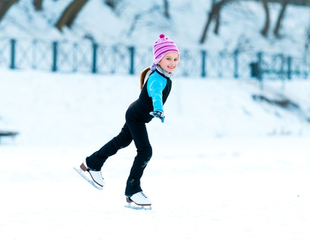cheerful happy little girl in thermal suits skating in winter outdoors