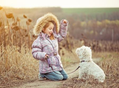 glückliches Mädchen mit ihrem Hund zu züchten White Terrier zu Fuß in einem Feld im Herbst