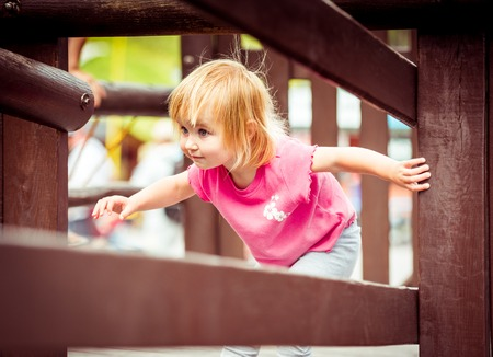 jungle gyms: happy little girl at the playground