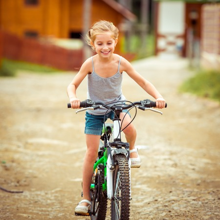 biker girl: happy little girl riding a bicycle in rural areas