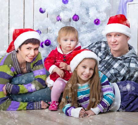 Christmas photo of a family in Santa caps around a decorated Christmas tree photo